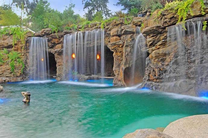 A luxurious pool with a waterfall and a cave at old lion for Pool design hamilton