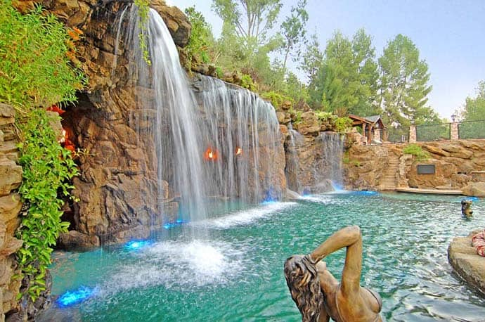 A luxurious pool with a waterfall and a cave at old lion for Pool design usa