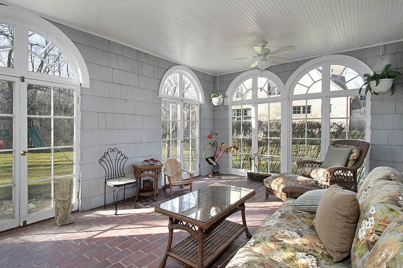 Sunroom in luxury home with view to back yard