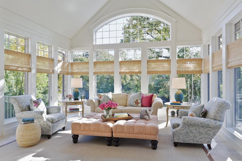 Beautiful white sunroom with pastel colors and three walls of floor to ceiling windows with cat on ottoman